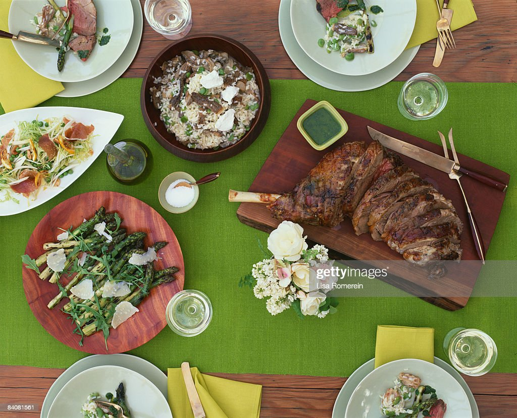 Table setting w/roasted leg of lamb & side dishes : Stock Photo