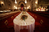 Table settings are laid out in the Palace Ballroom for a State Banquet at The Royal Welcome Summer opening exhibition at Buckingham Palace on July 23...