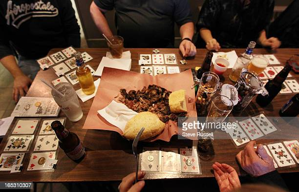 A table shares their winnings at Porketta Bingo at the Beef n Bird in Sudbury Porketta Bingo three cards are laminated together from a deck including...