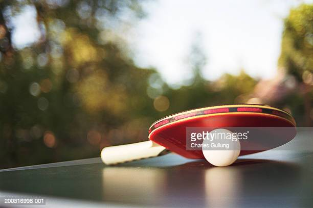 Table tennis paddle and ball on table outdoors, close-up