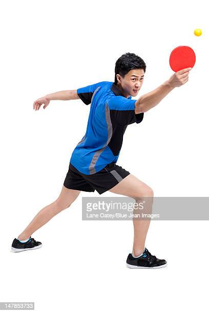Table tennis player bounces ball on paddle
