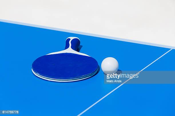 Table tennis racket and ball on a ping pong table
