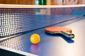 Table tennis - racket, ball, table. Tabletennis or ping pong rackets and yellow balls on blue table. Sport concept. Table tennis