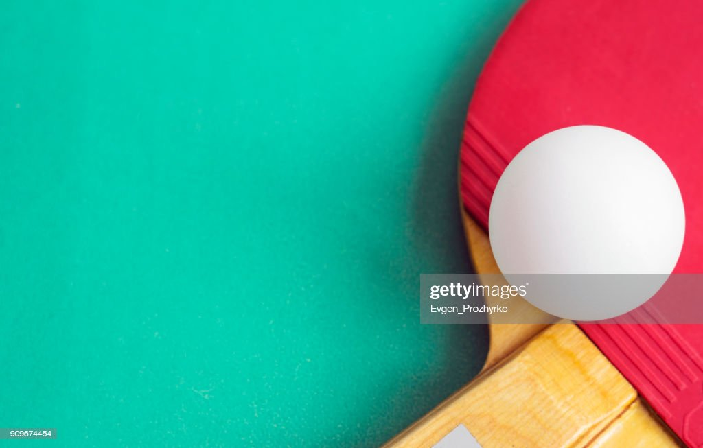 Table Tennis Racket With A Ball On Green Background. Ping Pong. Image With  Copy Space, Selective Focus.