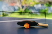 Table tennis table with racket and orange ball on a blue table with net installed on backyard of the house in Australia, shallow DOF, focus on ball