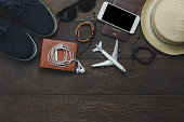 Table top view of essential item gentlemen for travel with technology background concept.Mix variety object on modern rustic wood office desk.Several  accessories for men travel to holidays trip.