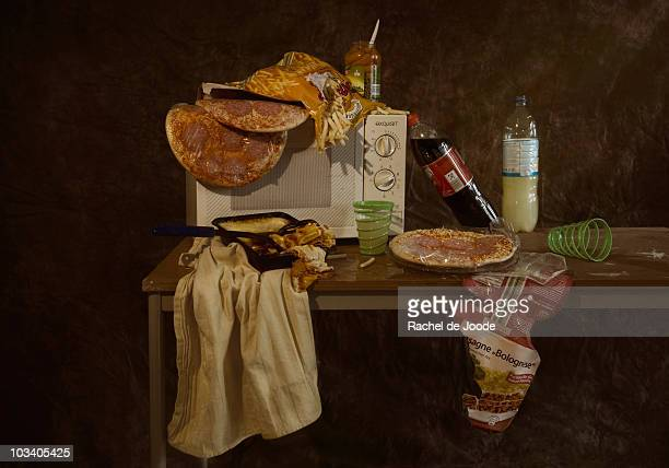 A table with a microwave and various frozen pizzas and frozen lasagna, still life