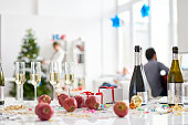 Full champagne flutes, apples, Christmas presents on table in office