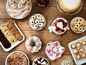 Table with cake, pies, cupcakes, tarts and cakepops. Studio shot on brown wooden background. Flat lay.