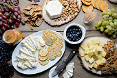 A table with fresh grapes, blueberries, brie, crackers, and honey, spread out for a party.
