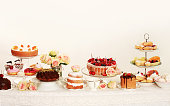 Table with loads of cupcakes, cake pops, birthday cakes, flowers and fruits. Light background