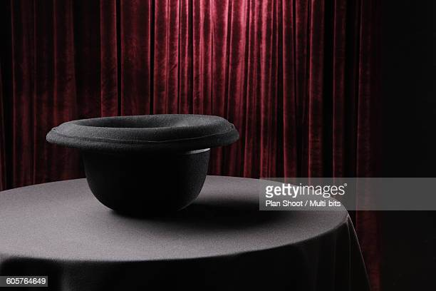 Table with inverted bowler hat on stage