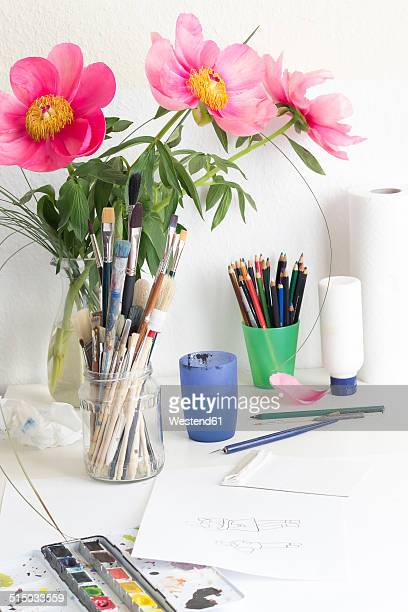 Table with pink peonies, Paeonia officinalis, and utensils for painting