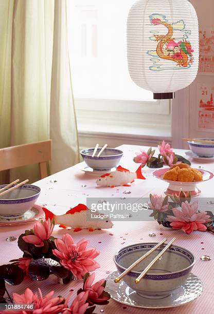 A table with place settings and Japanese decorations