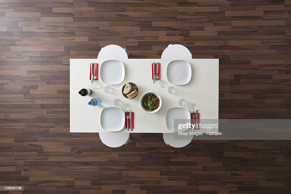 A table with place settings, wine, water, salad and bread, no people, overhead view : Stock Photo