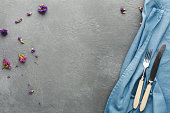 Blue linen tablecloth with silver knife and fork lying in the corner on gray textured table, decorated with violet flowers, top view, copy space. Mockup for cookbook