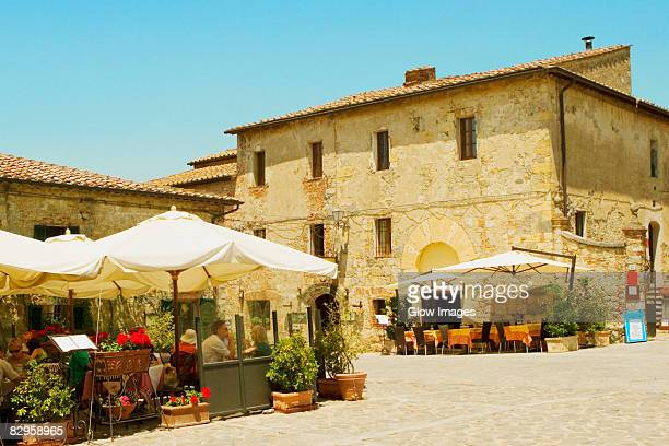 Tables and chairs at a sidewalk cafe, Piazza Roma, Monteriggioni, Siena Province, Tuscany, Italy