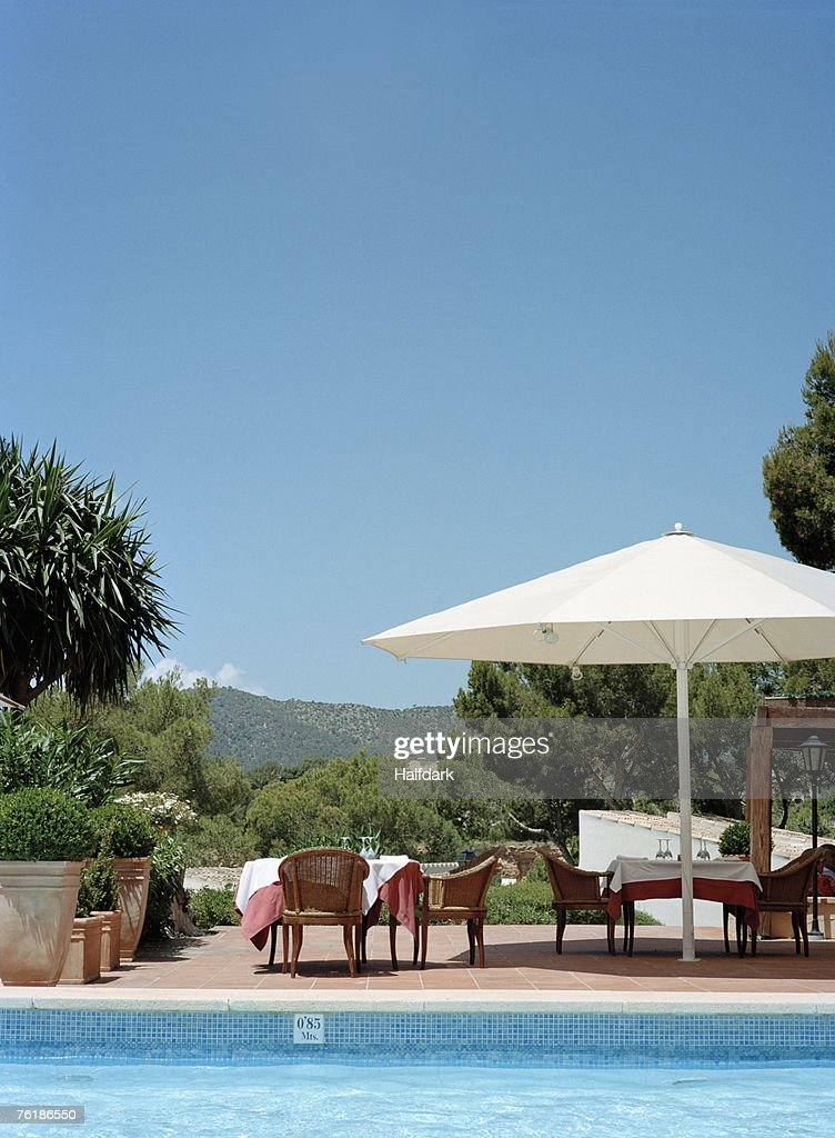Tables and chairs by a hotel swimming pool stock photo for Poolside table and chairs