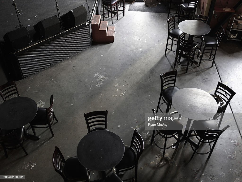 Tables and chairs in front of stage in nightclub, elevated view : Stock Photo
