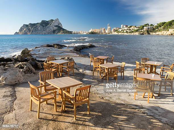 Tables and chairs of a terrace of bar close to the coast