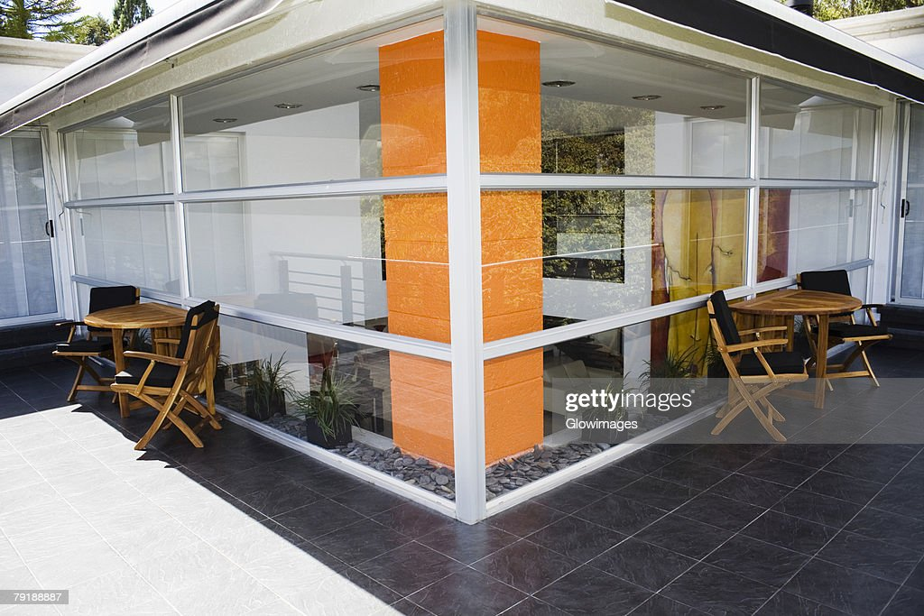 Tables and chairs outside a house : Stock Photo