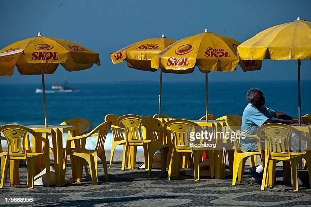 Tables and umbrellas displaying the logo for Cia de Bebidas das Americass Skol brand beer sit near Ipanema beach in Rio de Janeiro Brazil on Tuesday...