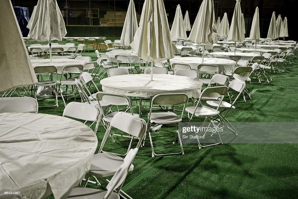 Tables, chairs and umbrellas set up at night : Stock Photo