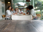 Empty table at a restaurant on the foreground and a dinner party at the background