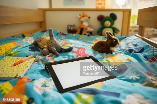 Room Filled With Soft Toys : Tablet computer and soft toys on bed in childrens room