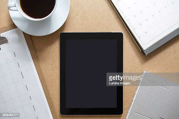 Tablet computer on table with clipboard and coffee