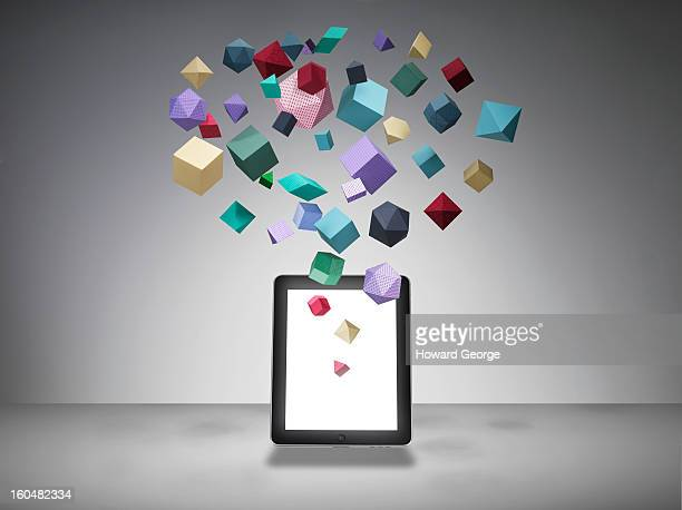 ipad with geometric shapes floating from screen