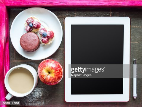 Tablet computer with tea cup, light meal in wooden tray : Stock Photo