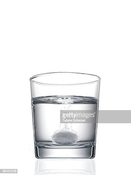 tablet fizzing in glass of water