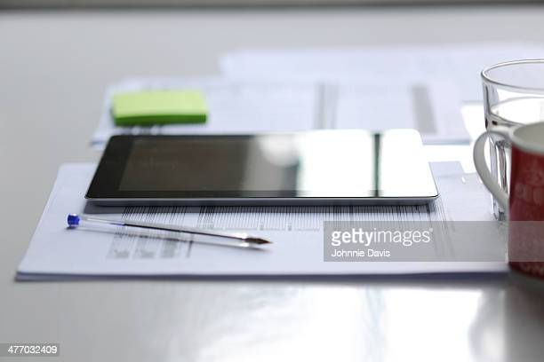 tablet on a desk with pen, drinks and paper work