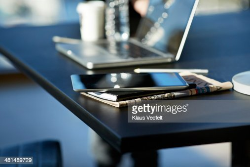 Tablet on top of notebook and newspaper