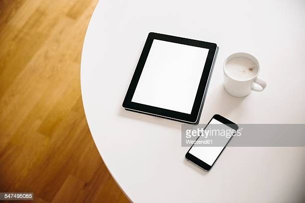 Tablet PC and smart phone with a cup of coffee on a white round table