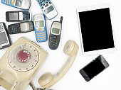 Tablet with smart phone and old phones on white background