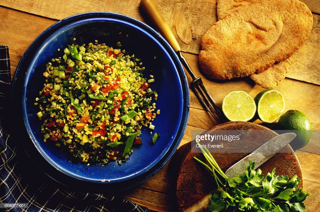 Tabouleh (Lebanon) salad in blue bowl beside pitta breads and limes : Stock Photo