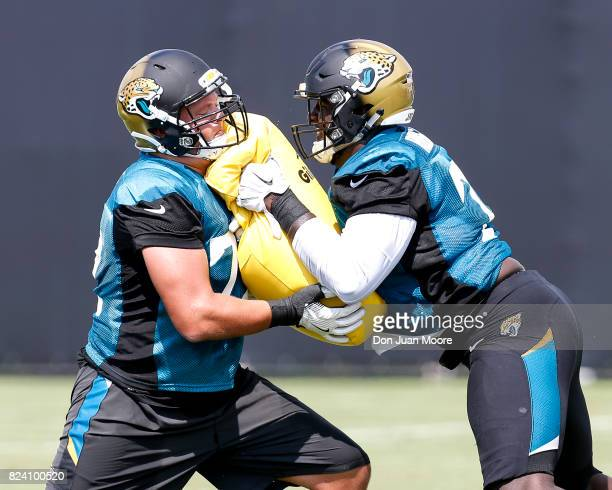 Tackles Josh Wells and Cam Robinson of the Jacksonville Jaguars works out during Training Camp at Florida Blue Health and Wellness Practice Fields on...