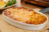 A chicken enchillada casserole topped with cheddar cheese