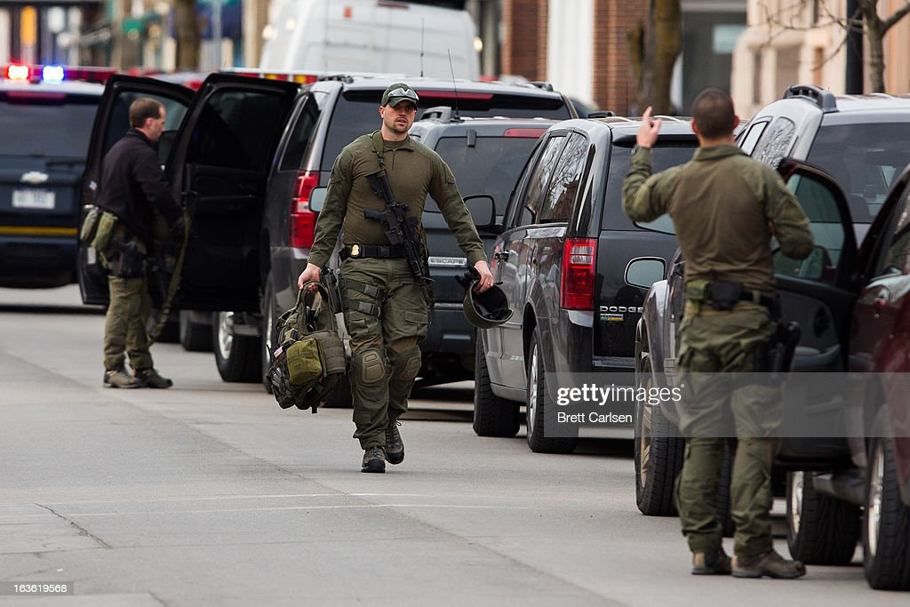 Tactical police officers return to their vehicles on North Main Street, equipment in hand, after waiting at the scene of a standoff with a murder suspect on March 13, 2013 in Herkimer, New York. Police have identified 64-year-old Kurt Meyers as a possible suspect responsible for a total of four shooting deaths and two injuries across the area earlier in the day.