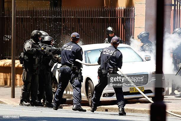 Tactical police use gas canisters and break the drivers side window to remove a man from his vehicle outside NSW Parliament House on Macquarie Street...