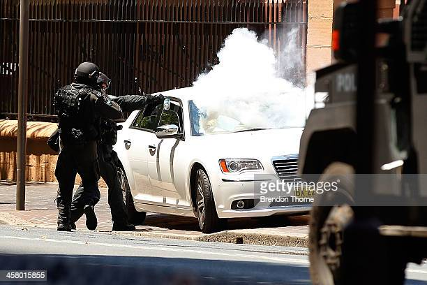 Tactical police use gas canisters to remove a man from his vehicle outside NSW Parliament House on Macquarie Street on December 20 2013 in Sydney...