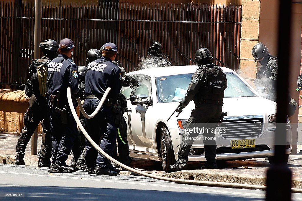 Tactical police use gas canisters to remove a man from his vehicle outside NSW Parliament House on Maquarie Street on December 20, 2013 in Sydney, Australia. The NSW Parliament House was locked down due to a security threat outside the building. A man has been apprehended after a stand off with riot police.