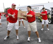 Tad Brown of the Houston Rockets along with Rockets players and staff members unload trucks of food and hand it out to victims of Hurricane Ike at a...
