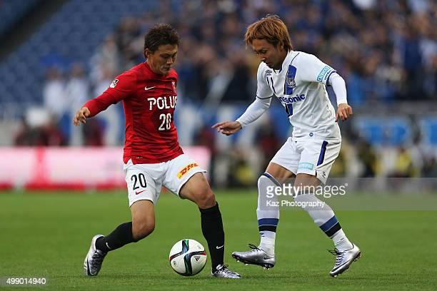 Tadanari Lee of Urawa Red Diamonds and Shu Kurata of Gamba Osaka compete for the ball during the JLeague 2015 Championship semi final match between...