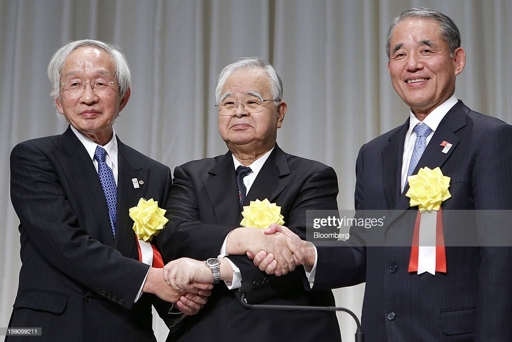Tadashi Okamura, advisor to Toshiba Corp. and chairman of the Japan Chamber of Commerce and Industry (JCCI), from left, Hiromasa Yonekura, chairman of Sumitomo Chemical Co. and chairman of the business lobby Keidanren, and Yasuchika Hasegawa, president of Takeda Pharmaceutical Co. and chairman of the business lobby Keizai Doyukai, shake hands as they pose for a photograph during a news conference following a New Year's party for business leaders in Tokyo, Japan, on Monday, Jan. 7, 2013. The Japanese government will announce around 12 trillion yen ($136 billion) in fiscal stimulus measures to boost the nation's shrinking economy, Japanese media reported today. Photographer: Kiyoshi Ota/Bloomberg via Getty Images