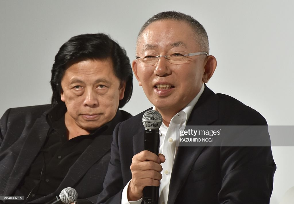 Tadashi Yanai (R), the president and CEO of Fast Retailing, the parent company of Japanese casual clothing chain Uniqlo, speaks as John Jay (L), Fast Retailing president of global creative, looks on during the UNIQLO 2016 fall-winter press preview in Tokyo on May 25, 2016. / AFP / KAZUHIRO