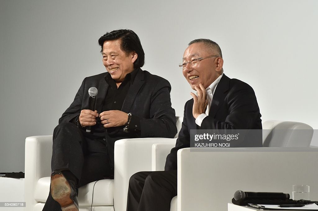 Tadashi Yanai (R), the president and CEO of Fast Retailing, the parent company of Japanese casual clothing chain Uniqlo, and John Jay (L), Fast Retailing president of global creative, speak during the UNIQLO 2016 fall-winter press preview in Tokyo on May 25, 2016. / AFP / KAZUHIRO