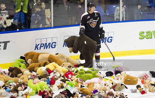 Taden Rattie of the Vancouver Giants picks up a teddy bear that was thrown on the ice during the annual 'Teddy Bear Toss' during the first period of...